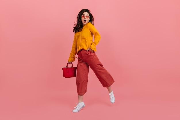 Ragazza vivace con gli occhiali alla moda guarda con stupore, camminando sul muro rosa. bruna in culottes e camicetta arancione in posa con la borsa rossa. Foto Gratuite