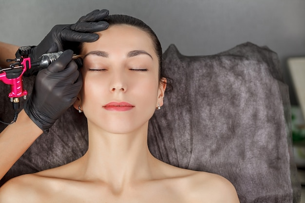 Процедура перманентного макияжа молодой девушке Premium Фотографии