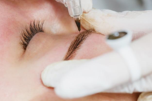 Перманентный макияж, татуаж бровей. косметолог в белых перчатках нанесения макияжа с машиной для женщины в салоне красоты Premium Фотографии