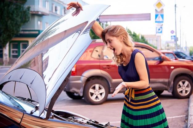 Perplexed girl near the car with an open hood. Premium Photo