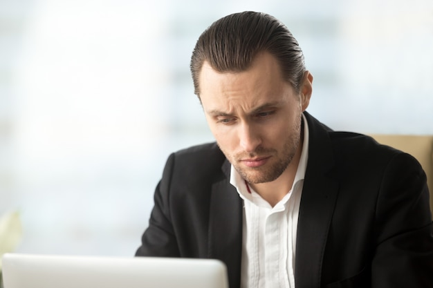 Perplexed young businessman looking at laptop screen Free Photo