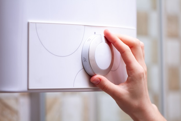 Person in bathroom is adjusting the temperature in the water heater Premium Photo