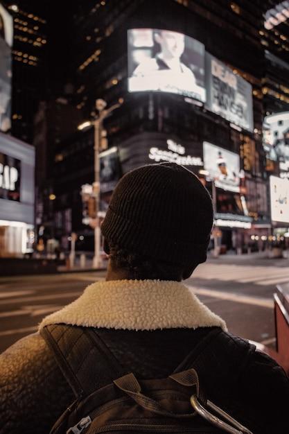 Persona in berretto in maglia nera e giacca marrone in piedi sulla strada durante la notte Foto Gratuite