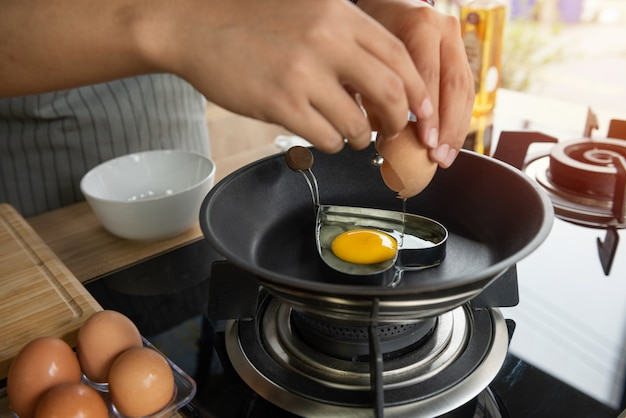 Person breaking an egg into heart mold in a pan Free Photo