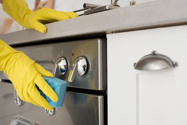Person cleaning the kitchen with gloves Free Photo