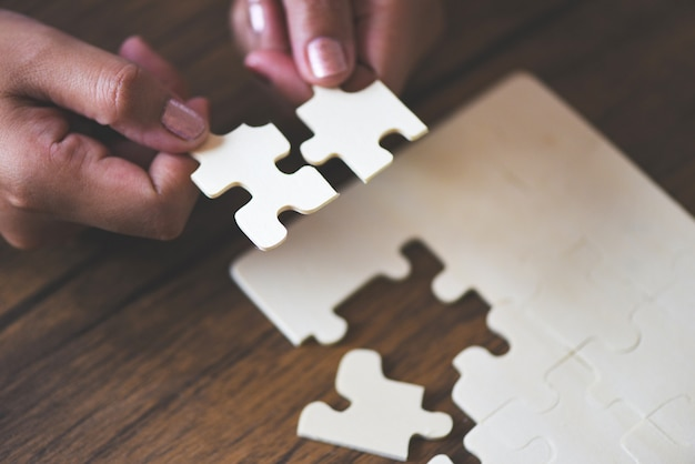Person connecting jigsaw pieces Premium Photo