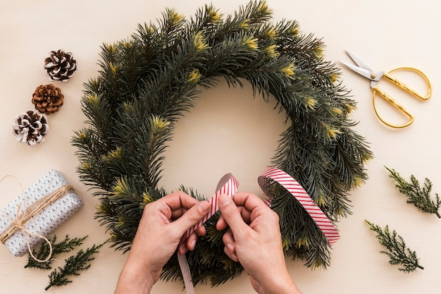 Person decorating christmas wreath with ribbon Free Photo