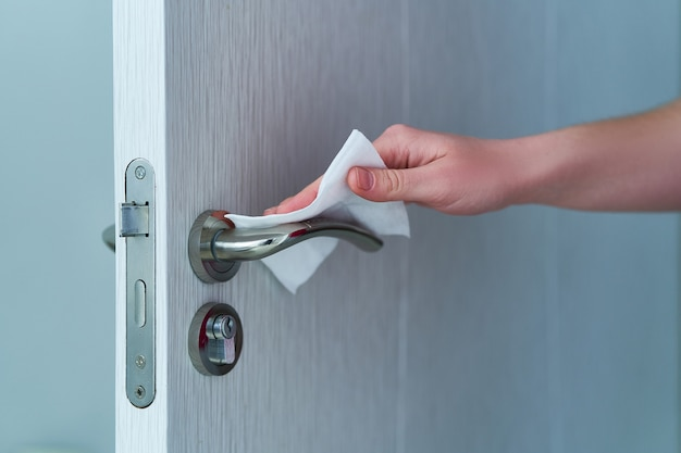 Person disinfects and cleans door handle with antibacterial wet wipes to protect against coronavirus outbreak Premium Photo