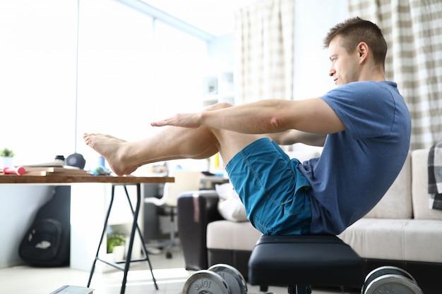 Человек делает упражнения в гостиной Premium Фотографии
