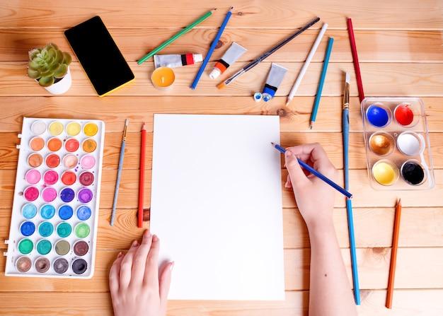 Рисунок и живопись. руки держат белую бумагу. вид сверху. Premium Фотографии