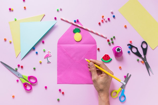 A person drawing on the envelope with decorative elements over pink background Free Photo