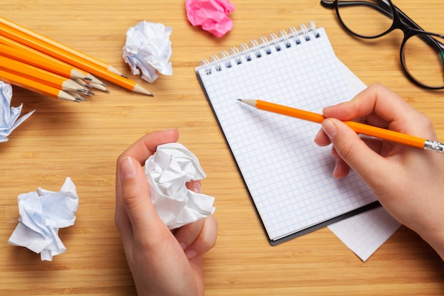 Person drawing in a notepad and office supplies on the table Premium Photo
