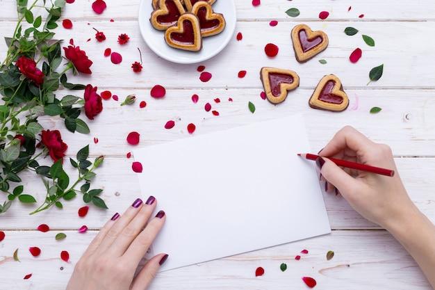 バラの花びらとハート型のクッキーの近くに赤鉛筆で白い紙に描く人 無料写真