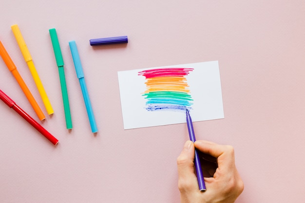 Person drawing rainbow with felt pen Free Photo