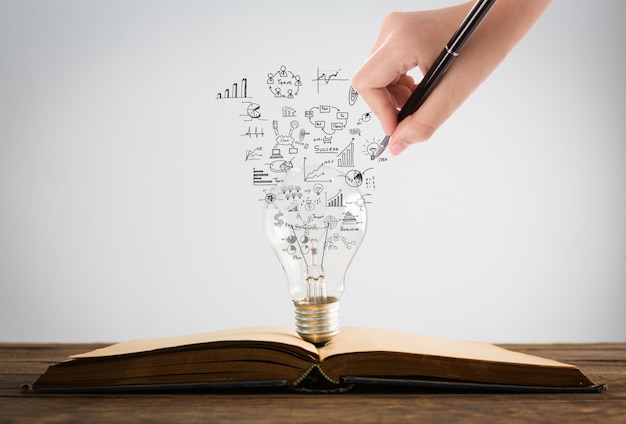 Person drawing symbols coming out of a light bulb on top of a book Free Photo