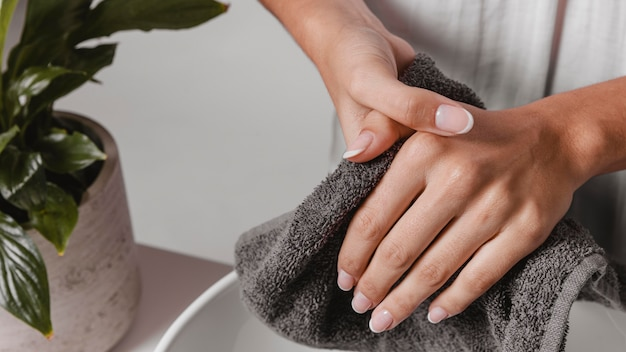 Person drying her hands on a towel close-up Free Photo