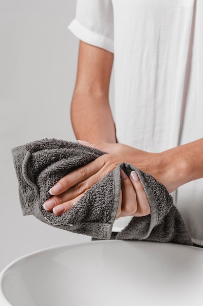 Person drying her hands on a towel Free Photo