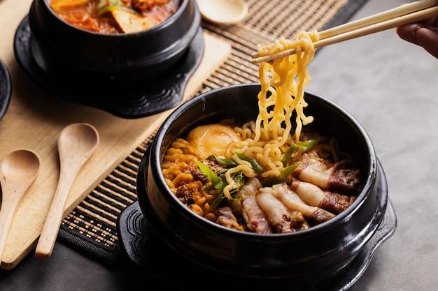 箸で黒い皿から中華料理を食べる人 無料写真