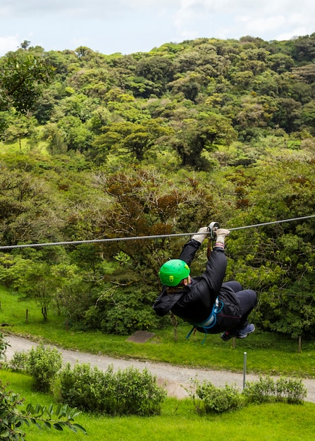 A person enjoying ride of zip line adventure in costa rica forest Free Photo