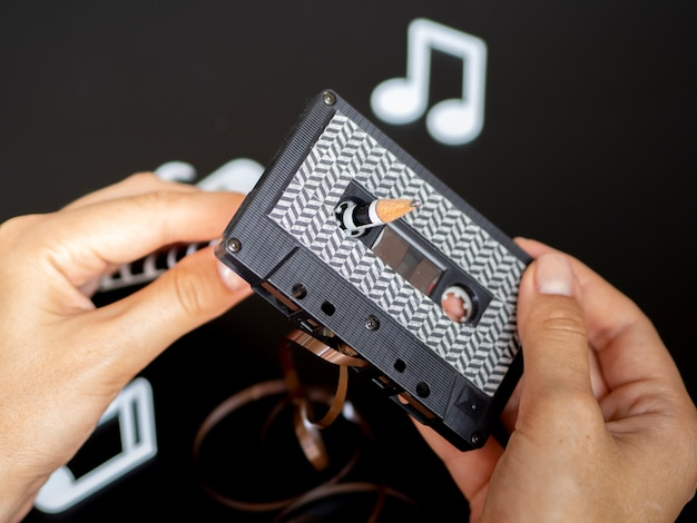 Person fixing up broken cassette tape Free Photo