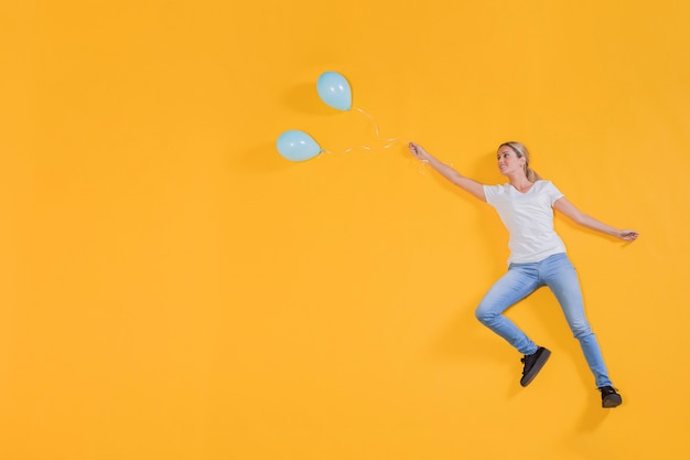 Person floating with blue balloons Free Photo