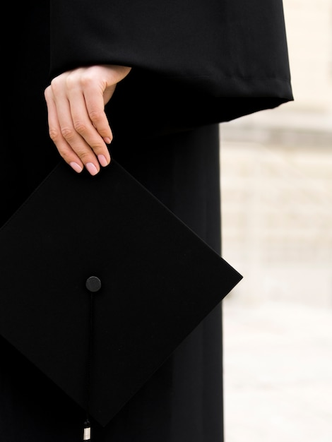 Person in graduation gown holding his cap Free Photo