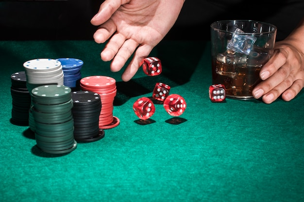 Person hand holding glass of whiskey while rolling red dice Free Photo
