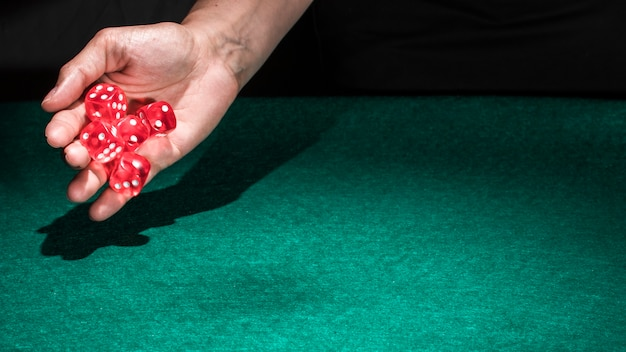 A person hand rolling red casino dice on green table Free Photo
