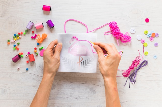 A person hand's doing embroidery with decorative elements on textured backdrop Free Photo