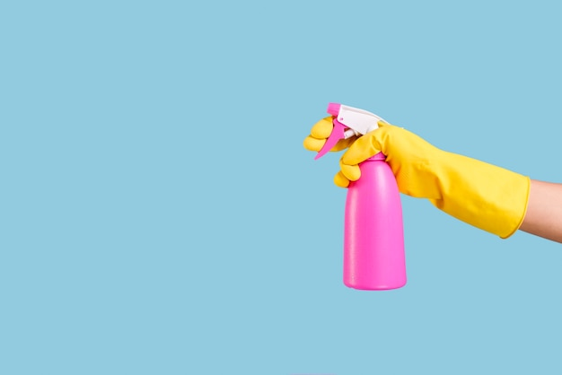 A person hand in yellow glove holding pink spray bottle on blue backdrop Free Photo