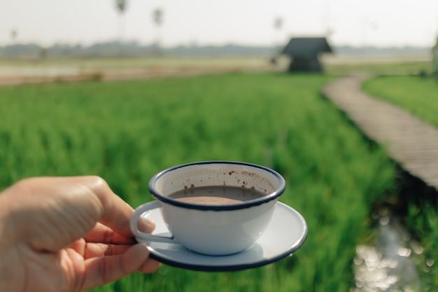 Человек держит кофе с видом на зеленое рисовое поле в концепции отдыха. Premium Фотографии