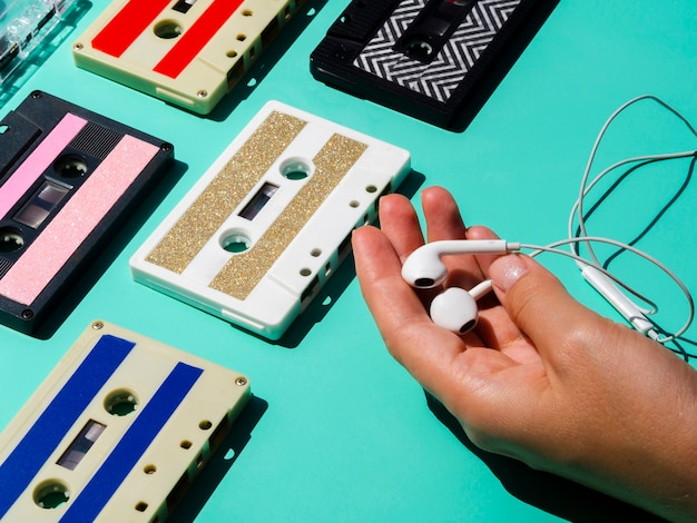 Person holdig headphones near cassette tape collection Free Photo