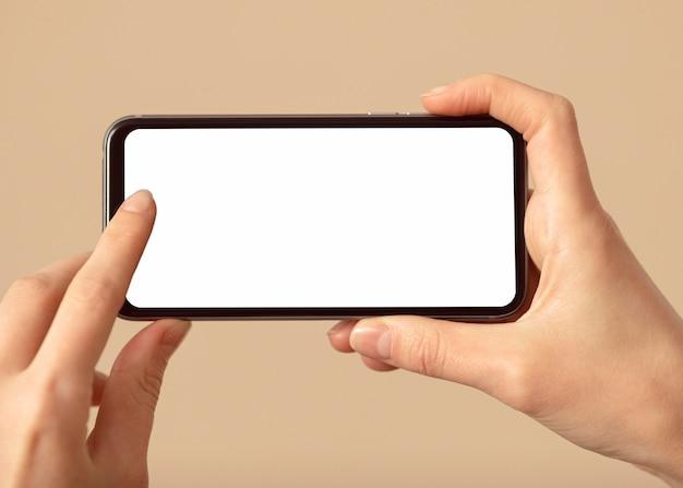白い画面の携帯電話を持っている人 無料写真