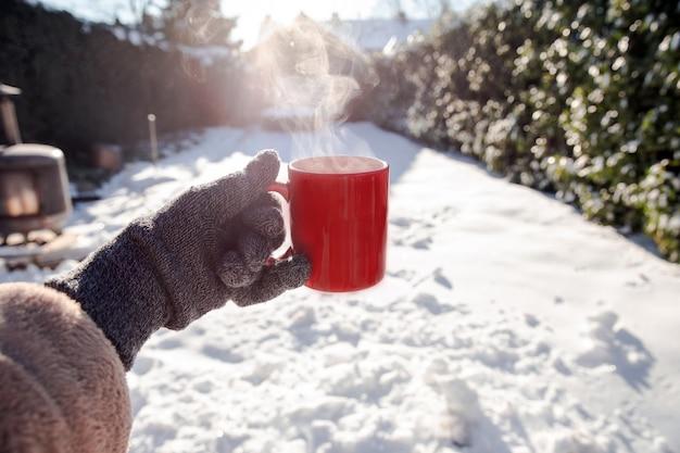 Человек, держащий красную кружку с горячим кофе с дымящимся дымом и перчатки в снегу Premium Фотографии