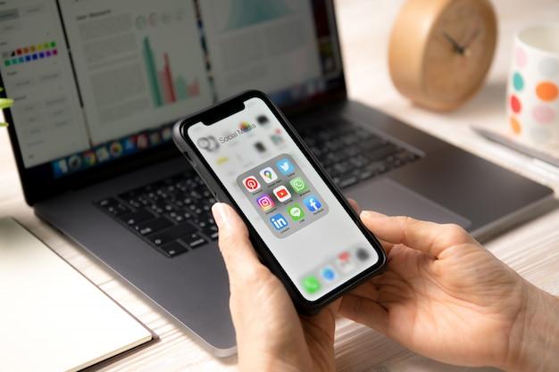 Лицо, занимающее смартфон с иконками социальных медиа на экране у себя дома Premium Фотографии