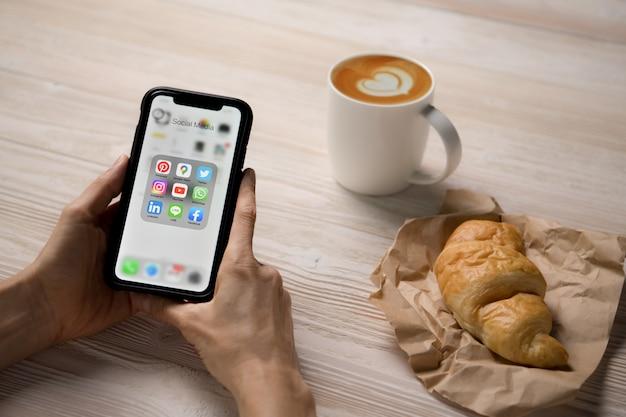 Лицо, занимающее смартфон с иконками социальных сетей на экране в кафе Premium Фотографии