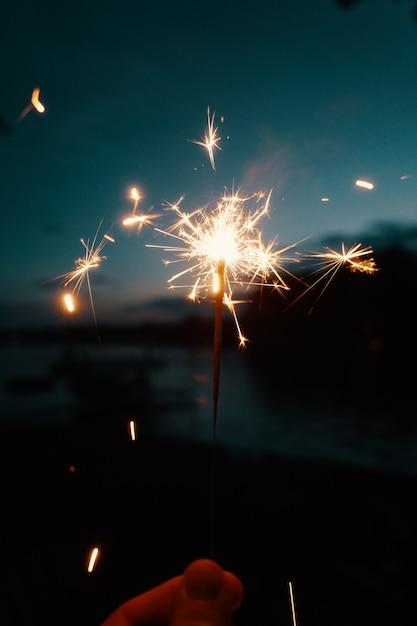 Лицо, занимающее бенгальские огни или бенгальские огни на темном фоне размыто Бесплатные Фотографии