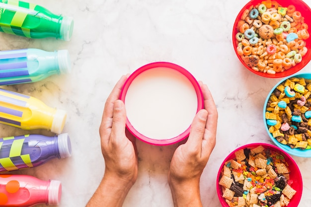 Person holding bowl with milk on table Free Photo