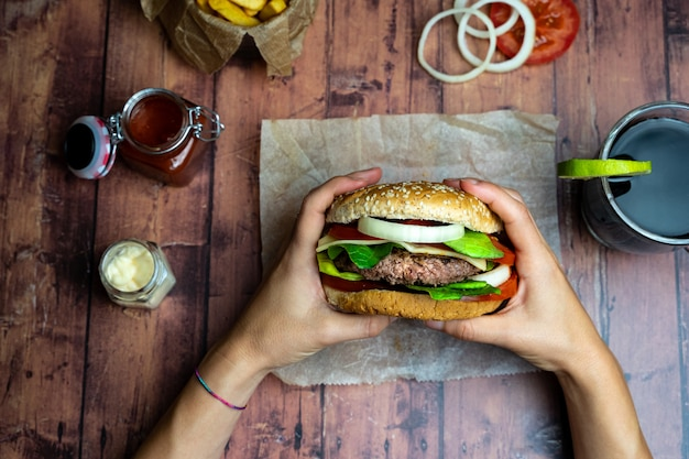 Person holding a burger with fries, onion rings and tomato on wooden table Premium Photo