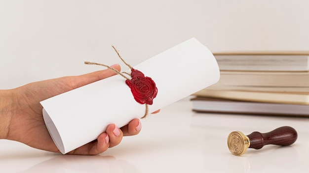 Person holding certificate next to wax seal Premium Photo