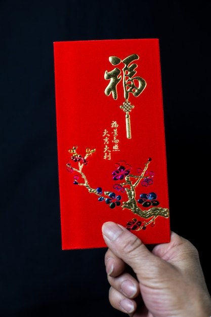 Person holding a chinese traditional red envelop for the celebration of chinese new year Free Photo