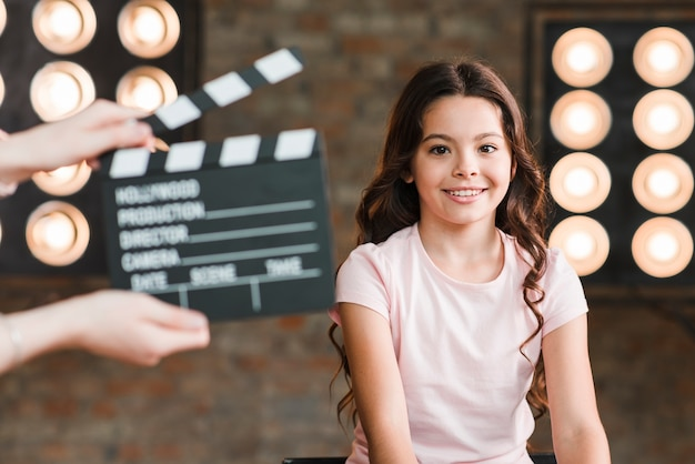 A person holding clapper board in front of smiling girl Premium Photo