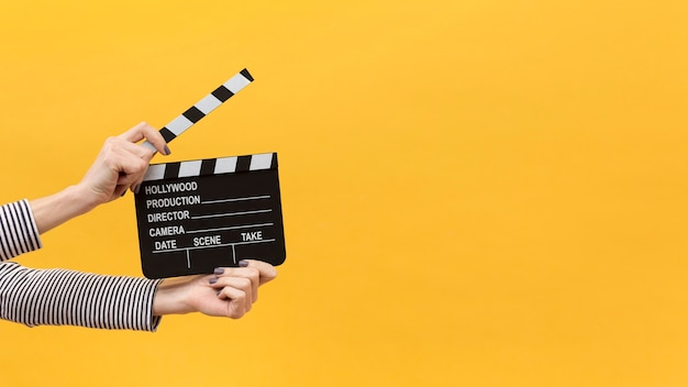 Person holding a clapper board on yellow background Premium Photo