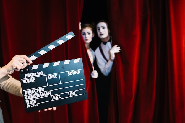 A person holding clapperboard in front of mime couple standing behind the red curtain Free Photo
