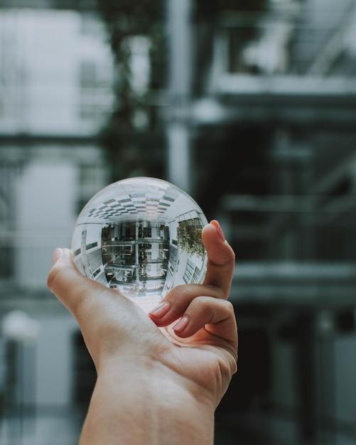 Una persona in possesso di una sfera di cristallo trasparente con il riflesso di un edificio Foto Gratuite