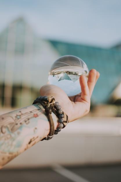Persona in possesso di una sfera di cristallo trasparente con il riflesso di un edificio triangolare Foto Gratuite