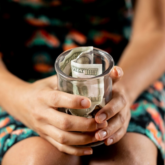 紙幣の入った透明な瓶を持っている人 無料写真