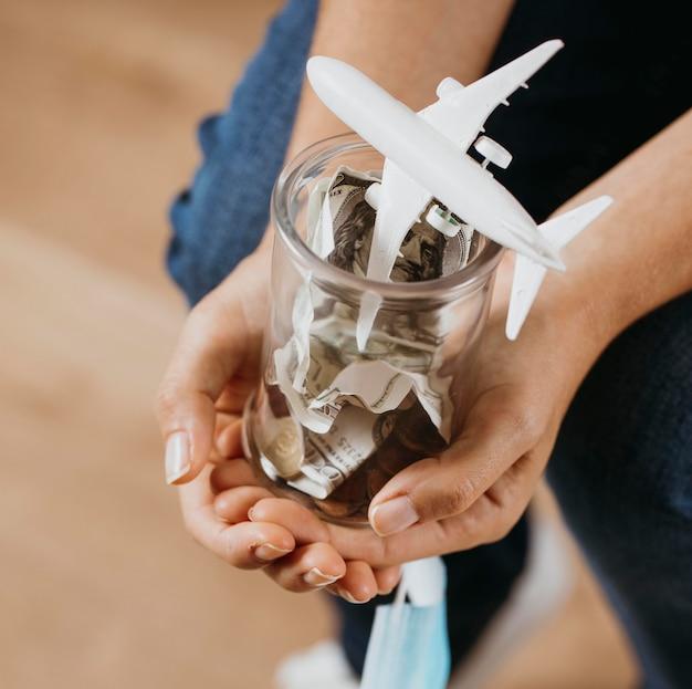 お金と飛行機の置物で透明な瓶を持っている人 Premium写真