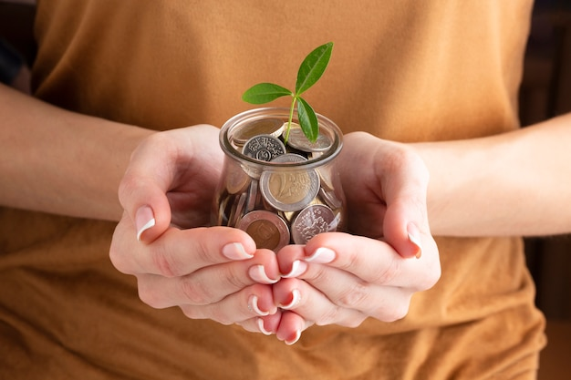 Person holding coin jar with plant Free Photo