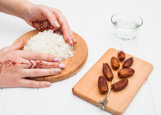 Person holding cooked rice on board near dates fruit Free Photo